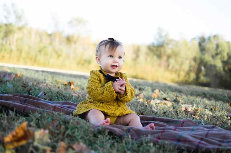 baby wearing yellow crochet long sleeve dress sitting on brown textile